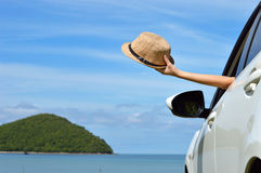 Happy woman on summer travel vacation. Woman shows sun hat from car window Stock Photos