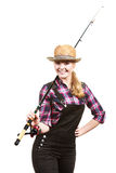Happy woman in sun hat holding fishing rod. Spinning, angling, cheerful fisherwoman concept. Happy woman in sun hat holding fishing rod, having fun and smiling royalty free stock image