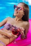 Happy woman sunbathing while lying on air mattress in the pool. Sunbathing in pool. Happy woman wearing red sunglasses sunbathing while lying on air mattress in royalty free stock image