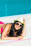 Happy woman sunbathing at swimming pool Stock Photos