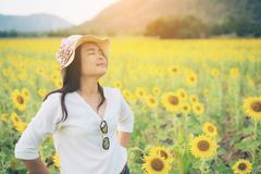 Happy woman in sunflower field smiling with happiness. Due to healthy food. Happy people, health care and agriculture business concept. Happy farmer or farm Stock Photos