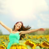 Happy woman in sunflower field. Summer girl in flower field cheerful and joyful. Multiracial Asian Caucasian young woman dancing, smiling elated and serene Royalty Free Stock Photography