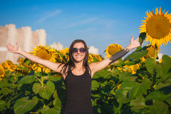 Happy woman in a sunflower's field Stock Photos