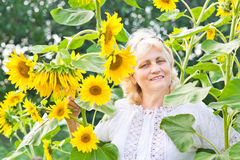 Happy woman with sunflowers in her garden Stock Image