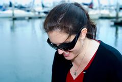 Happy woman with sunglasses. Portrait of happy young woman with sunglasses; sea and yacht marina in background Stock Image