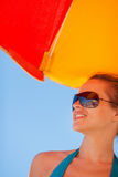 Happy woman in sunglasses on beach. Looking on copy space Stock Image