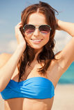 Happy woman in sunglasses on the beach. Picture of happy woman in sunglasses on the beach Stock Photography