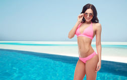 Happy woman in sunglasses and bikini on beach. People, fashion, swimwear, summer and beach concept - happy young woman in sunglasses and pink swimsuit looking at Stock Image
