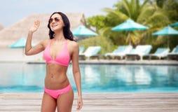 Happy woman in sunglasses and bikini on beach. People, swimwear, summer, travel and gesture concept - happy young woman in sunglasses and pink swimsuit waving Royalty Free Stock Photos