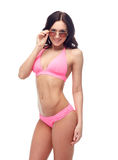 Happy woman in sunglasses and bikini swimsuit. People, fashion, swimwear, summer and beach concept - happy young woman in sunglasses and pink swimsuit looking at Stock Images