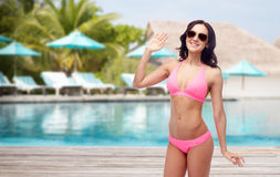Happy woman in sunglasses and bikini swimsuit. People, travel, tourism, swimwear and summer holidays concept - happy young woman in sunglasses and pink swimsuit Royalty Free Stock Image