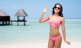 Happy woman in sunglasses and bikini swimsuit. People, travel, tourism, swimwear and summer holidays concept - happy young woman in sunglasses and pink swimsuit Royalty Free Stock Photography