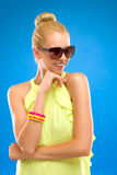 Happy woman in sunglasses on blue background. Stock Photos