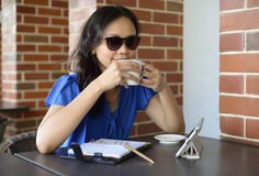 Happy woman with sunglasses drink in Cafe Stock Images
