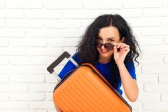 Happy woman in sunglasses holding travel suitcase. Emotional girl before trip isolated on white brick wall. Lifestyle, travel and stock images