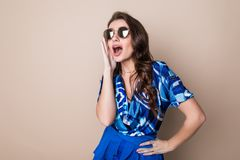 Happy young woman in sunglasses looking excited look at the camera on color studio background. Body language royalty free stock photo