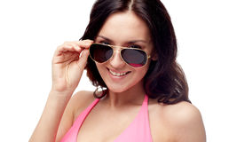 Happy woman in sunglasses and swimsuit. People, fashion, swimwear, summer and beach concept - happy young woman in sunglasses and pink swimsuit looking at you Stock Images