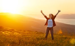 Happy woman on sunset in nature iwith open hands. Happy woman on the sunset in nature in summer with open hands royalty free stock photo