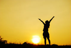 Happy woman and sunset silhouette Stock Photo