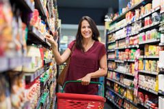 Happy woman at supermarket. Happy mature woman looking at camera while shopping in grocery store. Casual woman choosing food from shelf in supermarket and Stock Photo