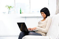 Happy woman surfing the internet from home Stock Images