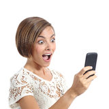 Happy woman surprised looking her smart phone. Isolated on a white background Royalty Free Stock Photography