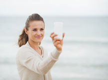 Happy woman in sweater on beach taking photo using cell phone Royalty Free Stock Image