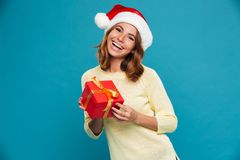 Happy woman in sweater and christmas hat holding gift box. And looking at the camera over blue background Stock Photos