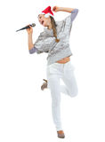 Happy woman in sweater and christmas hat singing in microphone Stock Images