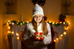 Happy woman in sweater holding glowing gift box at Christmas eve Royalty Free Stock Photos