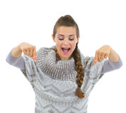 Happy woman in sweater pointing down Royalty Free Stock Photography