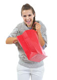 Happy woman in sweater pulling out something from shopping bag Stock Images