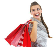 Happy woman in sweater with shopping bags looking on copy space Stock Images