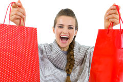Happy woman in sweater showing red shopping bags Royalty Free Stock Photography