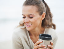 Happy woman in sweater sitting on beach with cup of beverage Royalty Free Stock Photography