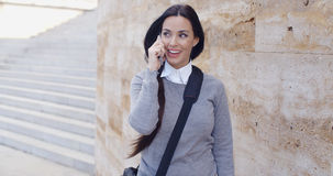 Happy woman in sweater talking on phone Stock Photography