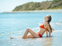 Happy woman in swim suite laying on sea shore Royalty Free Stock Photo