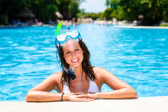 Happy woman swimming in tropical resort pool. Happy woman with snorkel gear swimming in tropical resort pool and enjoying relaxing vacation Royalty Free Stock Photos
