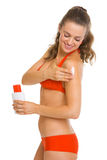 Happy woman in swimsuit applying sun block creme Stock Photo
