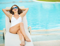 Happy woman in swimsuit laying on chaise-longue Stock Photo