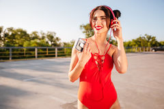 Happy woman in swimsuit listening to music from old player Royalty Free Stock Image