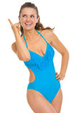 Happy woman in swimsuit pointing up on copy space Royalty Free Stock Photo
