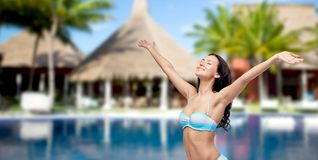 Happy woman in swimsuit with raised hands on beach Stock Image