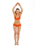 Happy woman in swimsuit ready to jump in water. Happy young woman in swimsuit ready to jump in water Royalty Free Stock Image