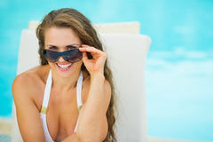 Happy woman in swimsuit relaxing on chaise-longue Royalty Free Stock Photos