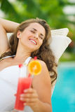 Happy woman in swimsuit relaxing with cocktail Royalty Free Stock Image