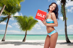 Happy woman in swimsuit with sale sign on beach Royalty Free Stock Photography