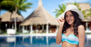 Happy woman in swimsuit and sun hat on beach. People, fashion, summer vacation and travel concept - happy young woman in bikini swimsuit and sun hat over Royalty Free Stock Photography