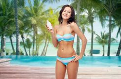 Happy woman in swimsuit with sunscreen on beach Stock Photos
