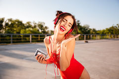 Happy woman in swimwear listening to music and singing outdoors Royalty Free Stock Photo